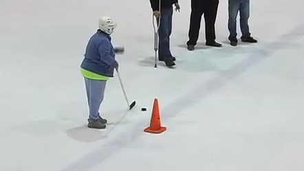 Watch this 59 year-old lady win a Ford truck with an insane hockey shot