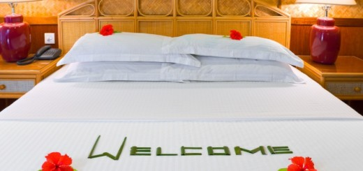 Word Welcome made of palm leafs and flowers on bed