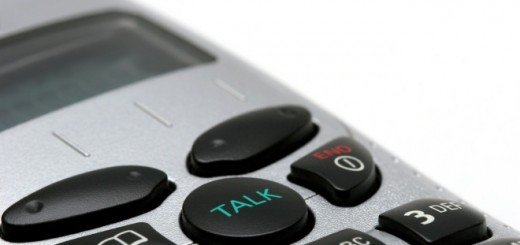 "macro of a wireless phone handset over white, focus on ""talk"" button"