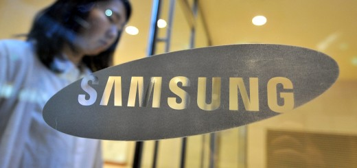 A woman walks past a logo of Samsung Ele
