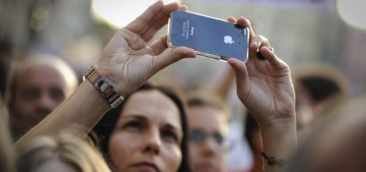 A woman takes a photo with her iPhone du
