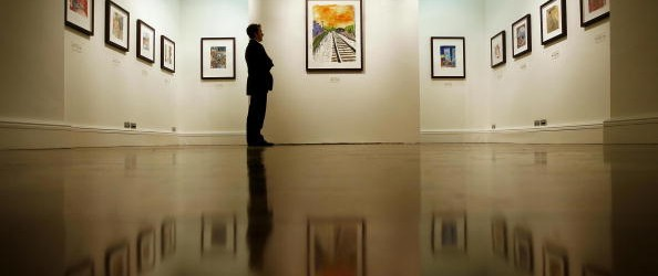 A visitor looks at a painting entitled '