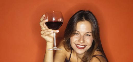 Partygoer holding glass of red wine