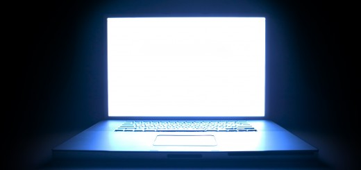 shot of a laptop computer as the screen glows in the darkness