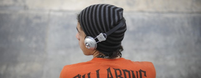 A skateboarder listens to music  at a pu