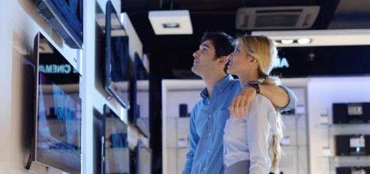 Young couple in consumer electronics store buy tv