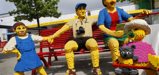 A family made of Lego bricks sit on a be