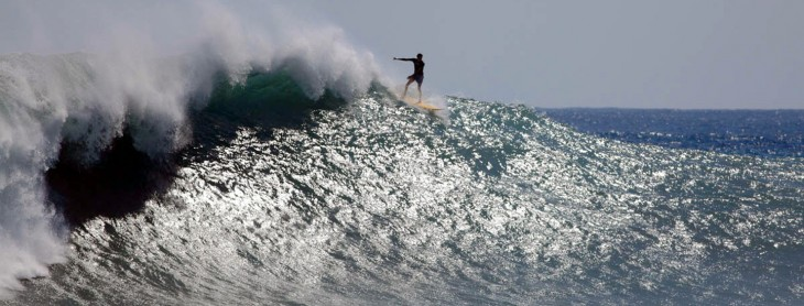 A surfer rides a wave at Le Port beach o