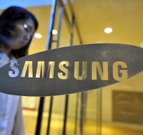 A woman walks past a logo of Samsung Ele