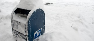 Snow blankets a USPS mailbox during a sn