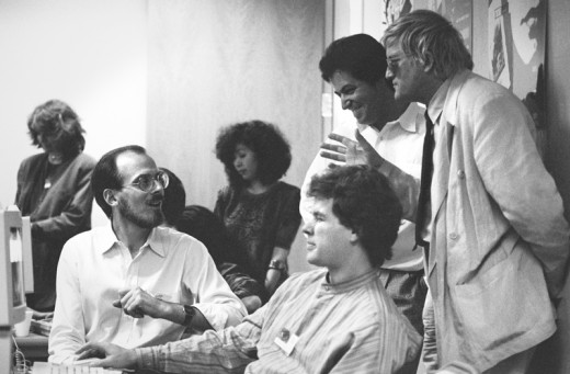 Adobe-Creative-Director-Russell-Brown-(left,-seated)-with-artists-Nicholas-Callaway-(center,-seated)-and-David-Hockney-(right,-standing)-and-other-colleagues-at-Adobe's-Art-Directors-Invitational,-1990