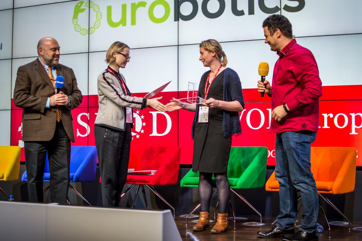 Anna Dvornikova, Managing Partner at TEC Ventures, passes the first prize to Jemma Redmond, CEO of Ourobotics