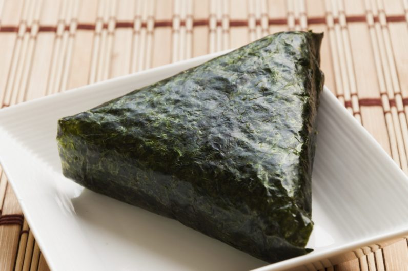 A piece of onigiri sitting in a shallow bowl