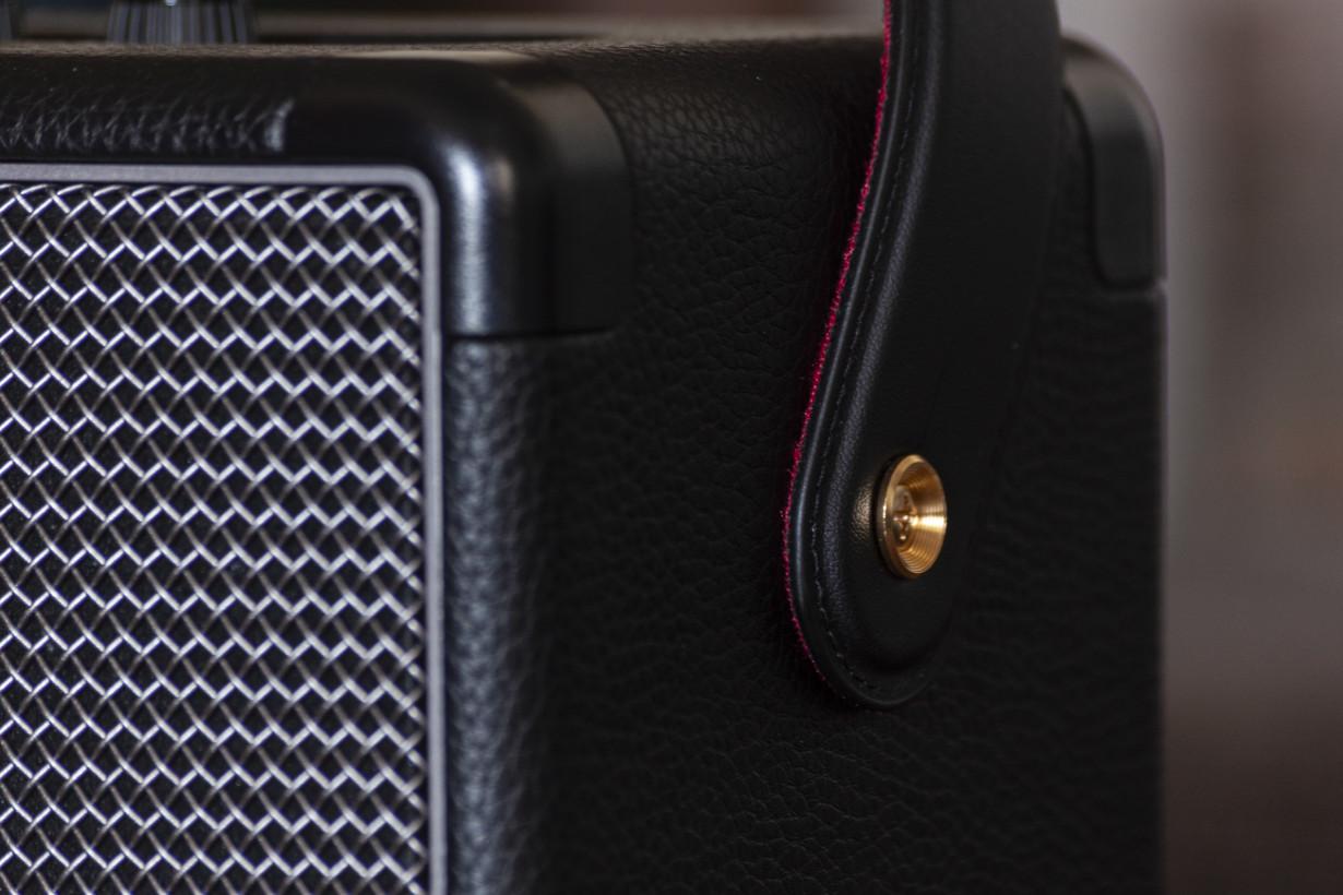 The strap and attachment button are reminiscent of guitar accessories