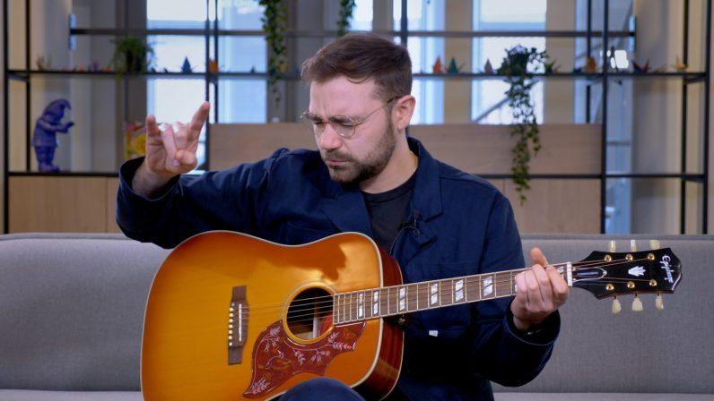 tocando la guitarra epiphone colibrí en el sofá