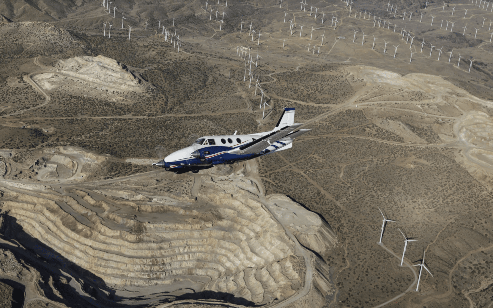 A King Air aircraft banks over the Mojave desert.