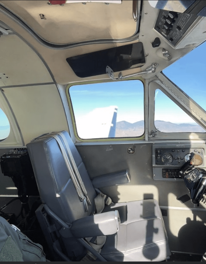 The cockpit of a King Air aircraft in flight with an empty pilot's seat