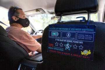 A guest rating and assistance sign hangs from the back of the passenger seat of Hector Castellanos' car, a Lyft and Uber driver of five years, as he drives in Walnut Creek, Calif. on Thursday, May 27, 2021.