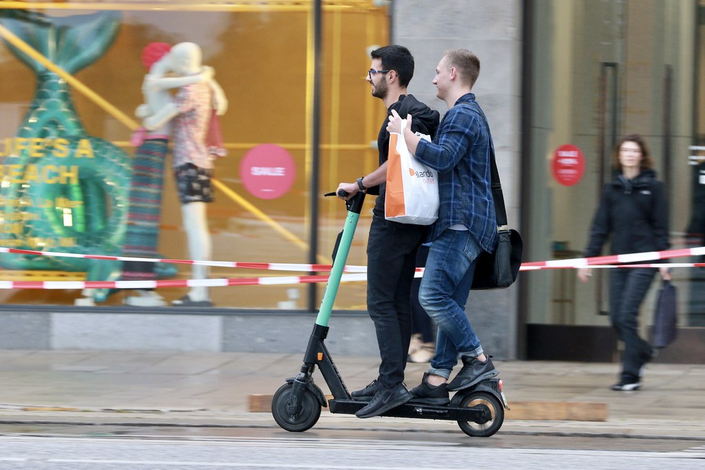 two people riding on the same scooter