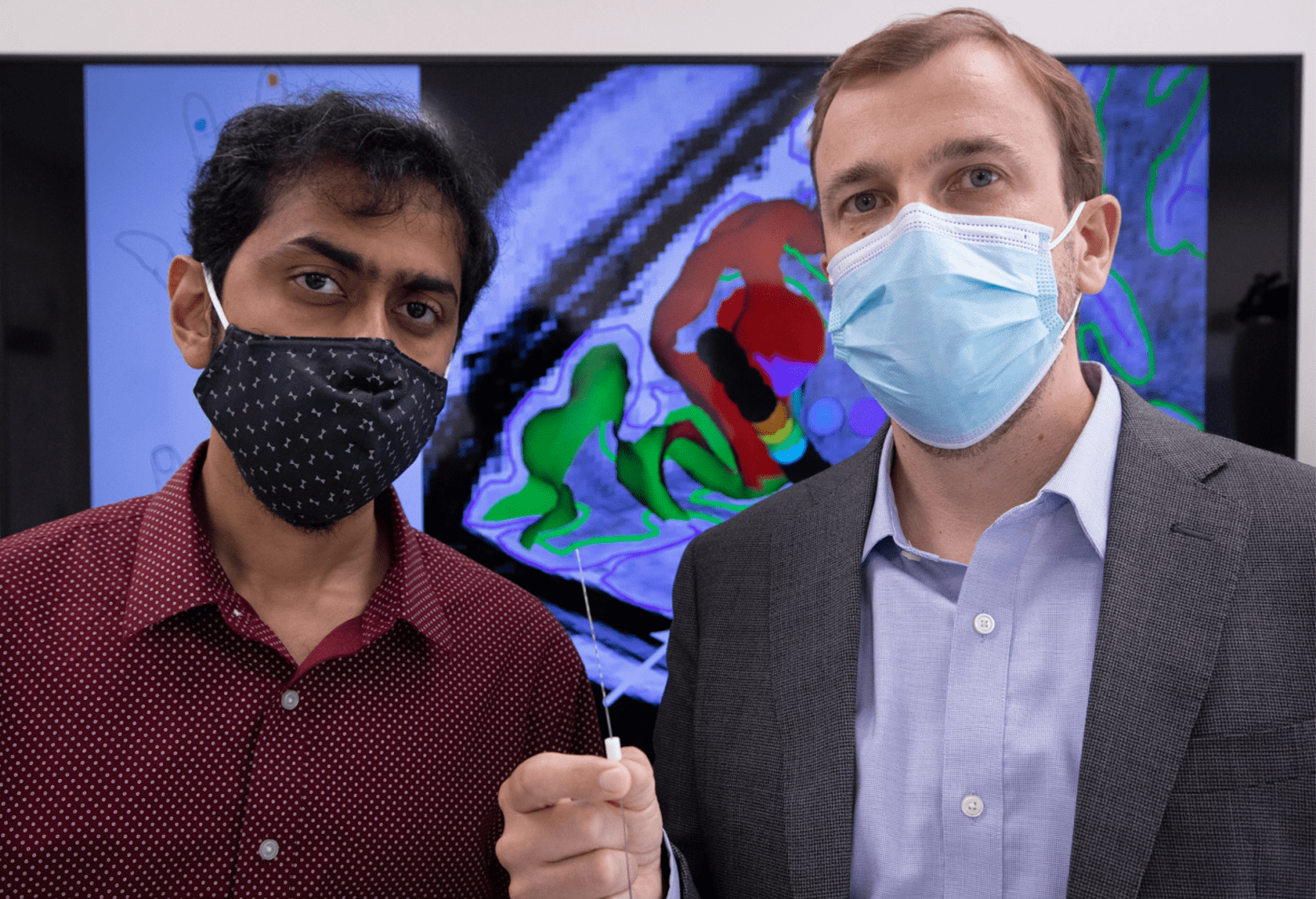 Santosh Chandrasekaran, PhD and Stephan Bickel, MD, PhD, co-lead authors on the paper hold up a SEEG electrode.
