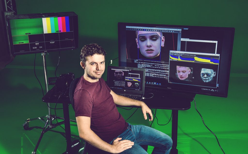 Chris Ume sitting in front of computer screens while creating deepfakes