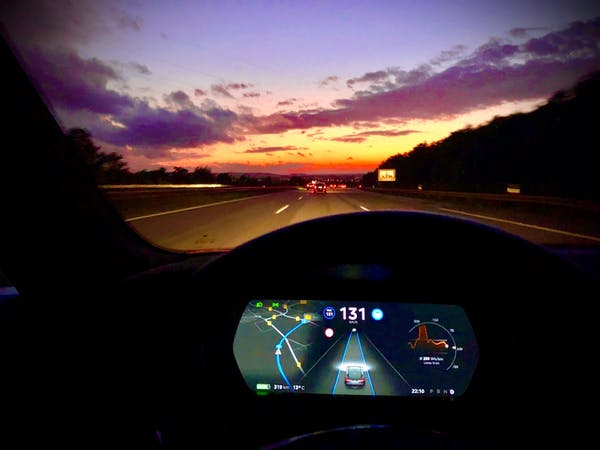 The dashboard seen from inside an electric car at sunset.