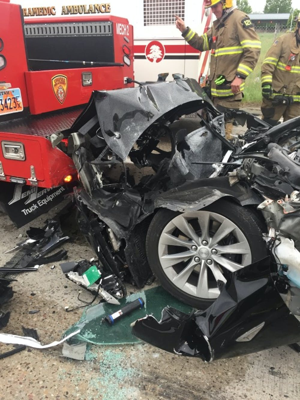Coche Tesla estrellado con el Departamento de Bomberos ayudando en el rescate
